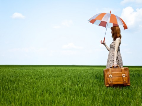 Redhead enchantress with umbrella and suitcase at spring wheat field.